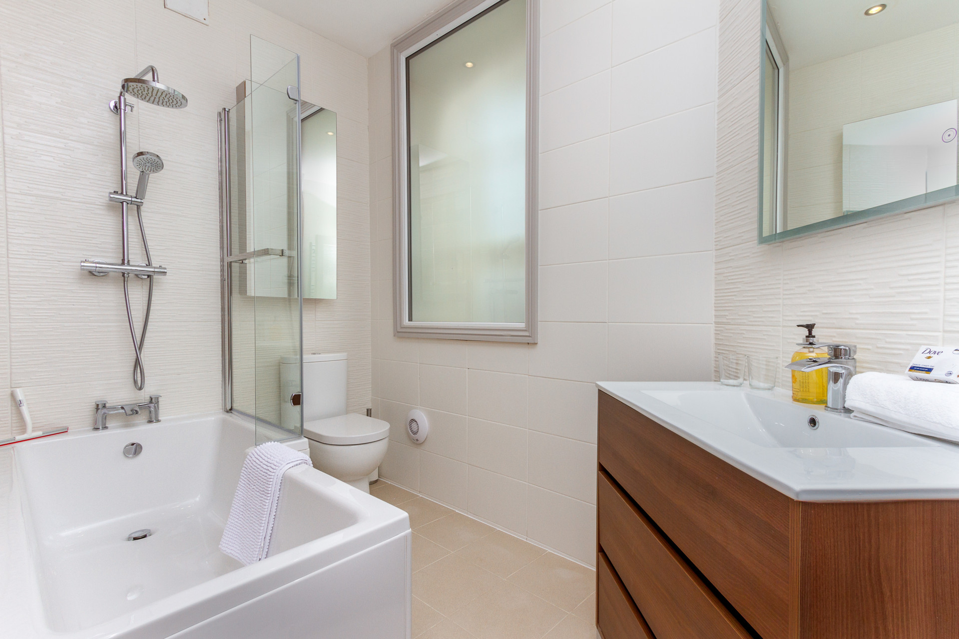 Bathroom with shower over bath, wc, and vanity basin unit